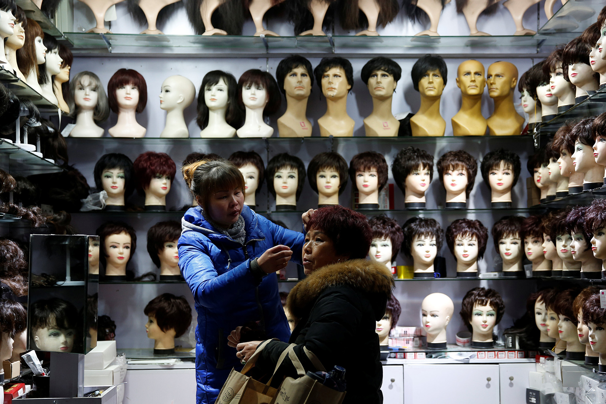 A vendor helps put on a wig on a customer at a wig shop near the central train station in Shanghai