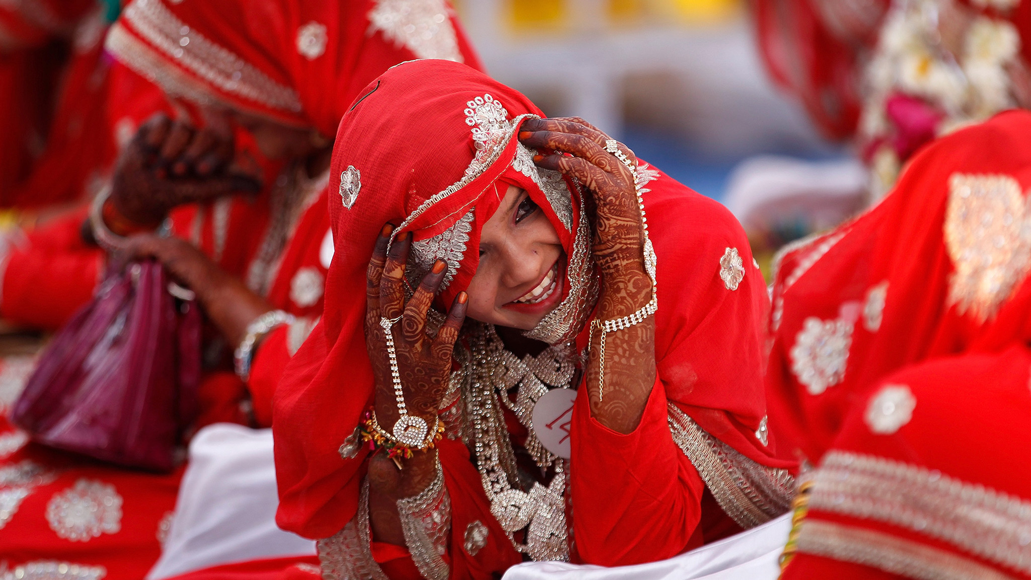 A bride reacts as she speaks with another bride during a mass marriage ceremony, in which, according to its organizers, 51 Muslim couples took their wedding vows, in Ahmedabad