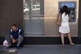 A man sits on the ground begging as a woman withdraws cash from an ATM in Malaga on June 27, 2014 (Jorge Guerrero/AFP/Getty Images)