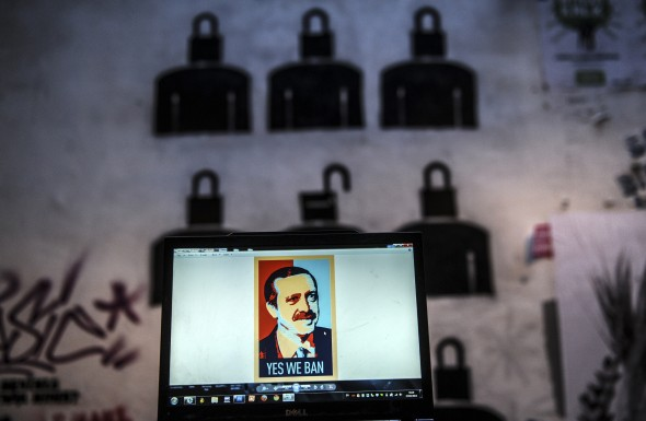 "A view of a computer screen showing a digital portrait of the Turkish Prime Minister Recep Tayyip Erdogan and text reading ""Yes we ban"" on a laptop computer screen, in front of graffiti in Istanbul, on March 27, 2014. AFP PHOTO / OZAN KOSE"