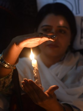 A woman lights a candle in tribute to the victims of the 16 February bomb at a Sufi shrine in Sindh province