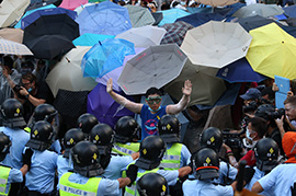 A pro-democracy demonstrator (centre) gestures in front of a police line near the Hong Kong government headquarters