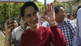 Myanmar pro-democracy leader Aung San Suu Kyi waves at supporters as she visits polling stations at her constituency