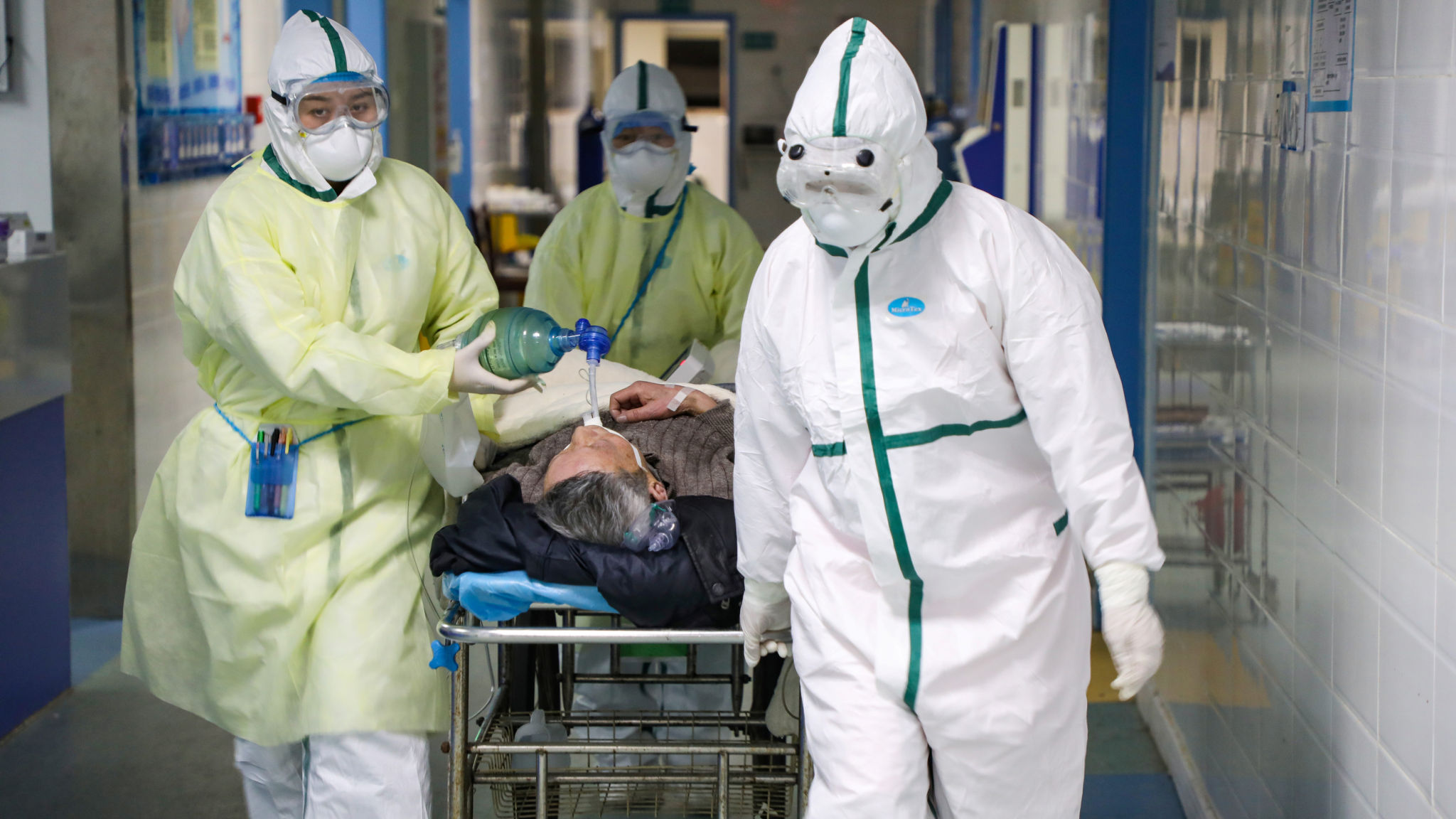 Medical workers in protective suits move a patient at an isolated ward of a hospital in Caidian district following an outbreak of the novel coronavirus in Wuhan
