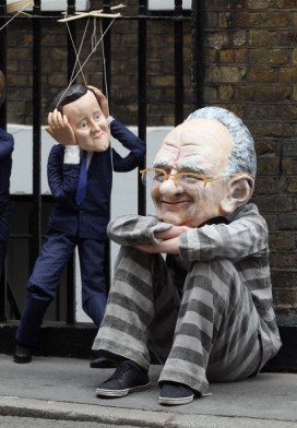 A puppet of David Cameron dances around a man dressed as Rupert Murdoch