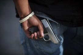 A gang member holds a gun behind his back