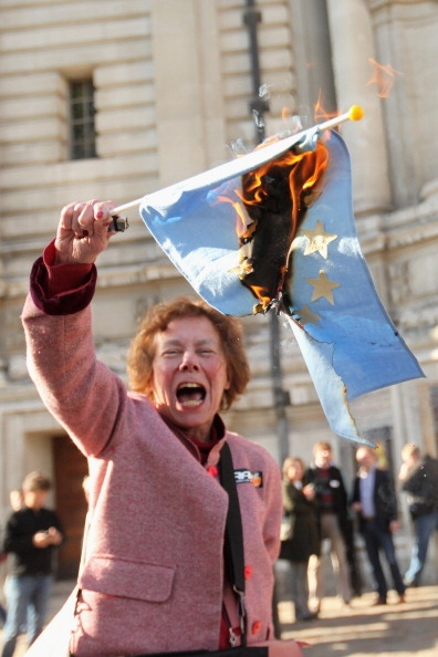 A British protester burns an EU flag
