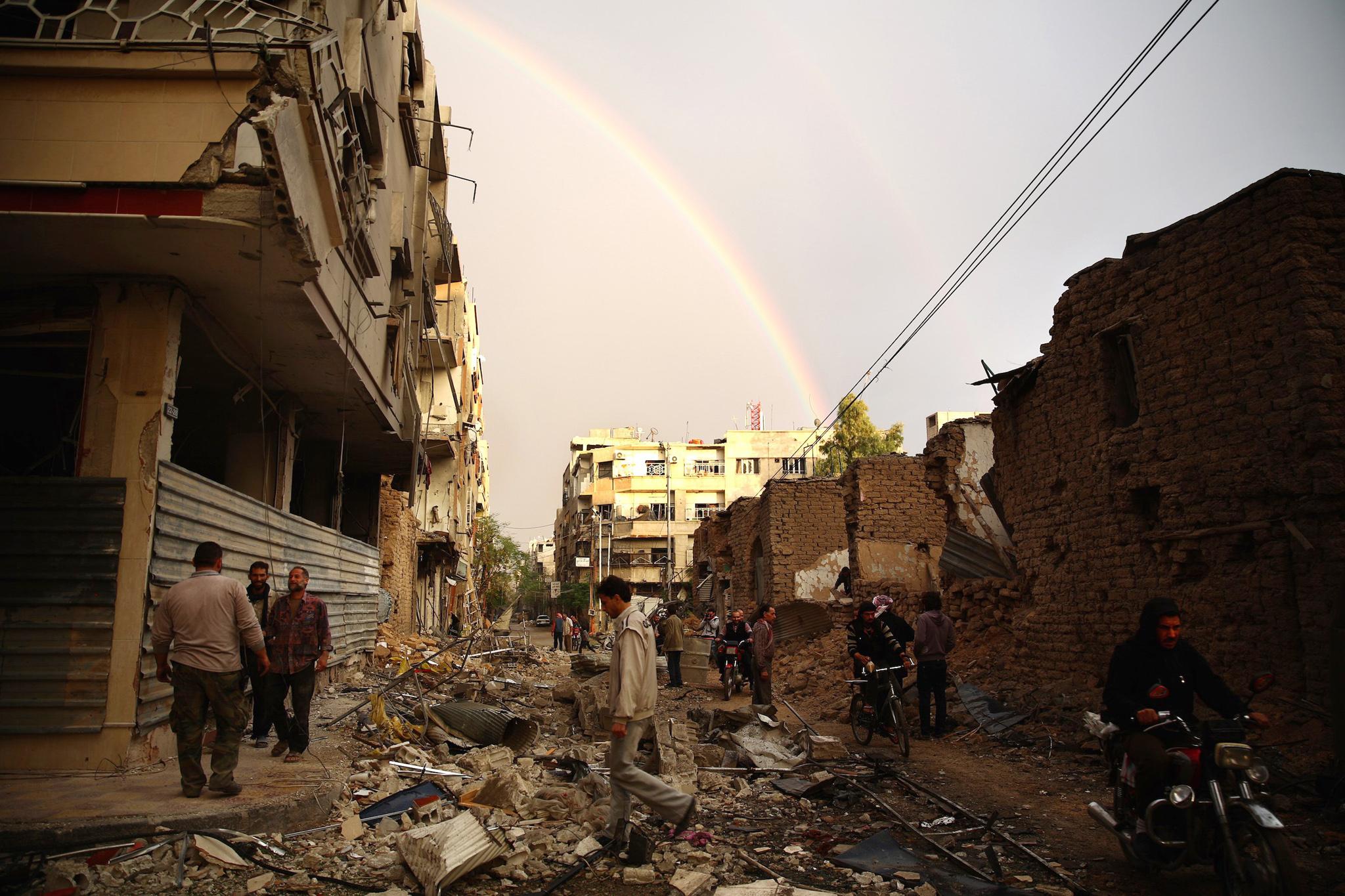 Residenti di Douma (Damasco) camminano tra i detriti dopo un attacco aereo delle forze governative siriane. Credit to: AFP/Getty Images